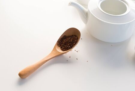 High angle view of white teapot with wooden spoon of rooibos tea on table (selective focus)