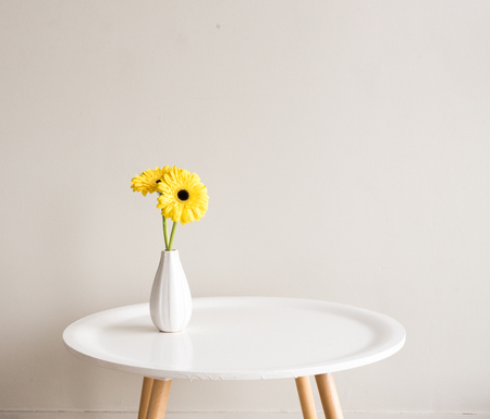 Yellow Gerberas In Small White Vase On Round Table Against Neutral  Background Photo
