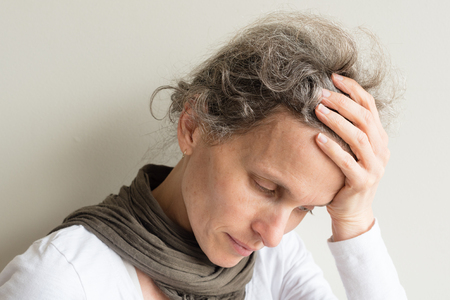 Head and shoulders view of middle aged woman with grey hair with hand on head looking despondent (selective focus) Foto de archivo
