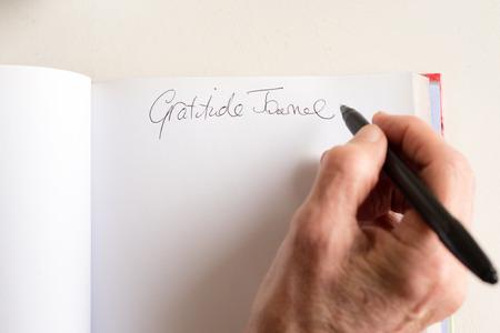Hoge hoekmening van oudere vrouw hand met zwarte pen en schrijven in dankbaarheid dagboek (selectieve aandacht)