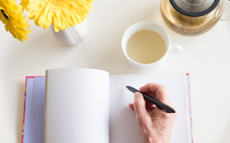 High angle view of older woman's hand holding black pen on blank journal with cup of chamomile tea and yellow flowers (selective focus)