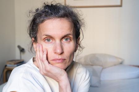 Portrait of despondent middle aged woman in bedroom (selective focus) Standard-Bild