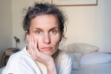 Portrait of despondent middle aged woman in bedroom (selective focus) Stock Photo