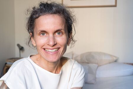 Portrait of happy smiling natural looking middle aged woman in bedroom (selective focus)