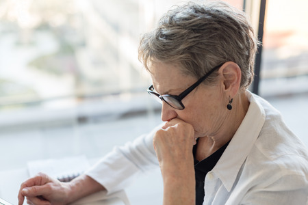 Profile of professional older woman with glasses concentrating at desk (selective focus)