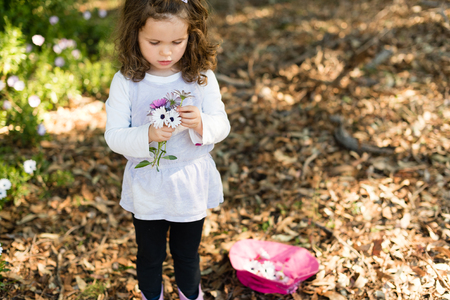 Little girl holding purple and white daisies next to pink hat filled with flowers (selective focus)
