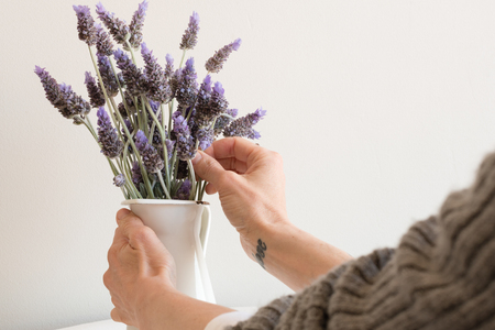 Cropped view of womans hands arranging lavender in small white jug (selective focus)