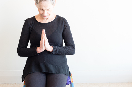 Cropped view of older woman with short grey hair and black clothing sitting on yoga stool with hands in prayer position