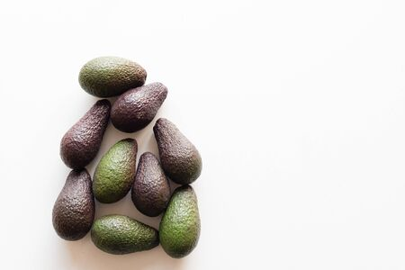 High angle view of organic green and black Hass avocados on white table background with copy space