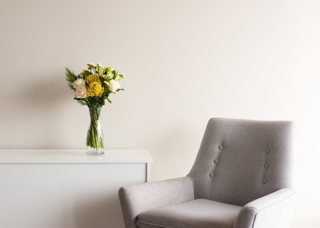 Close up of grey retro armchair next to white cabinet with cream and yellow flowers in glass vase against neutral wall background