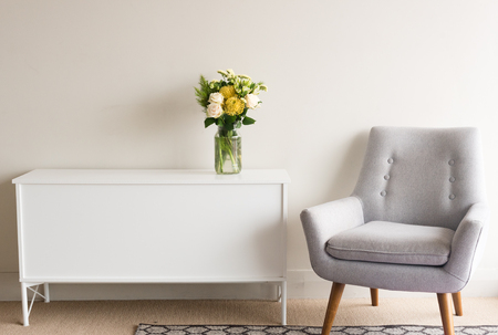 Grey retro armchair next to white sideboard with glass jar of cream and yellow flowers against neutral wall background Фото со стока