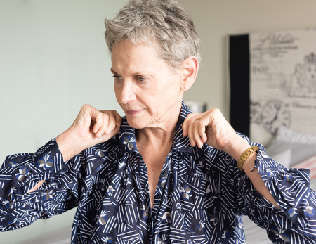 Head and shoulders view of older woman adjusting collar while getting dressed in bedroom (selective focus) Stock Photo