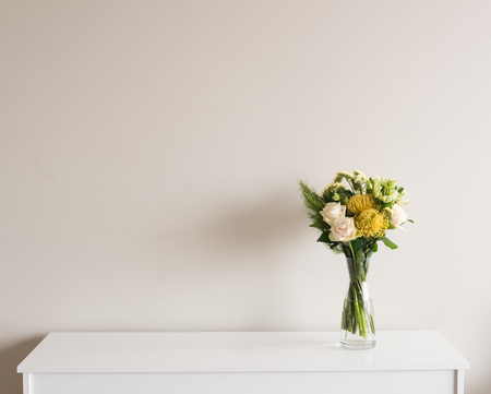 Yellow and cream flowers in glass vase on white sideboard against neutral wall background with copy space to left Foto de archivo