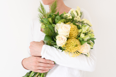 Cropped midsection view of woman holding bouquet of yellow and cream flowers against white background (selective focus) Stock Photo