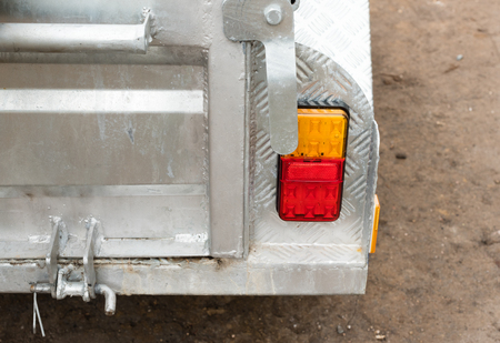 Close up cropped view of rear of car trailer door with brake and indicator lights (selective focus)
