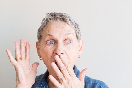 Head shot of beautiful older woman with short grey hair looking very surprised against neutral background (selective focus)
