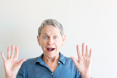 Head and shoulders view of beautiful older woman with short grey hair looking very surprised against neutral background (selective focus) Stock Photo