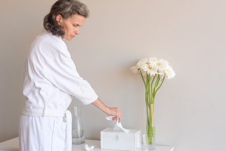 Mid length side view of middle aged woman with grey hair in white bathrobe taking tissue from box against neutral background