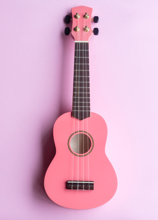 Directly above view of pink ukelele on pastel background Stock Photo