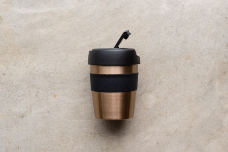 High angle view of reusable coffee cup on concrete background Foto de archivo