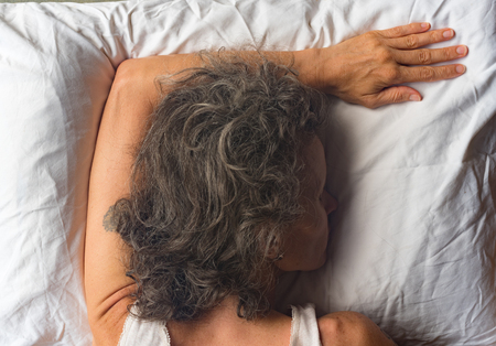 High angle close up  view of middle aged woman sleeping face down on pillow with arm overhead (selective focus) Stock Photo