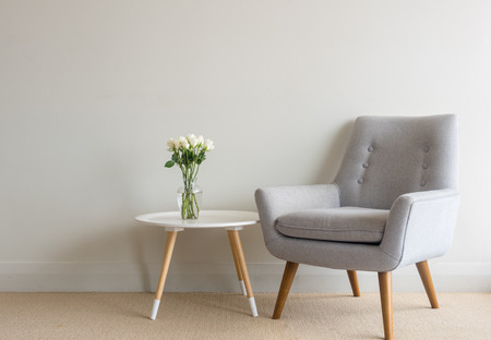 Retro Armchair And Small Round Table With White Roses In Glass Vase Against  Beige Wall Stock