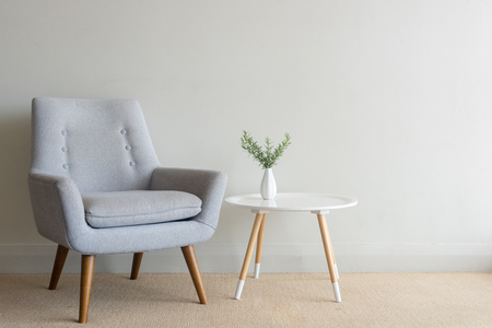 Retro armchair and small round table with rosemary in small vase against beige wall Foto de archivo