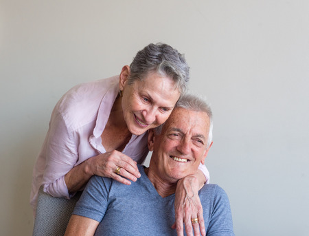 Beautiful older woman in pink shirt laughing with arms around seated older man against beige wall (selective focus)