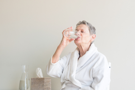 Older woman in white bathrobe seated and drinking glass of water against neutral background (selective focus)