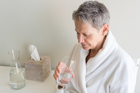 High angle view of older woman in white bathrobe drinking glass of water (selective focus)