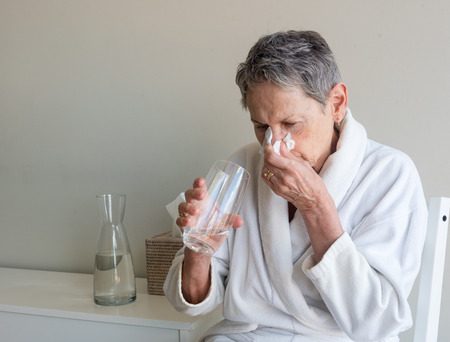 Older woman in white bathrobe seated and blowing nose with tissue while holding glass of water against neutral background (selective focus) Фото со стока
