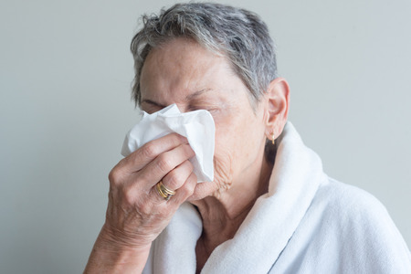Head and shoulders view of older woman in white bathrobe blowing nose with tissue against neutral background (selective focus)
