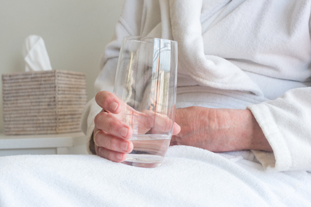 Close up view of older woman holding glass of water with tissue box in background (selective focus) 写真素材