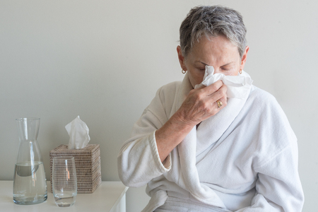 Older woman in white bathrobe seated and blowing nose with tissue against neutral background (selective focus)