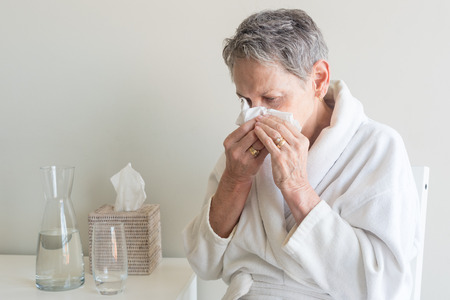 Side view of older woman in white bathrobe seated and blowing nose with tissue against neutral background (selective focus)