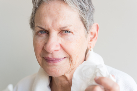 Close up of beautiful older woman in white bathrobe holding tissue (selective focus)