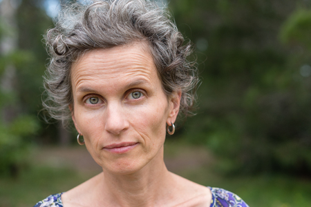 Middle aged woman with grey hair looking at camera against forest background (selective focus)