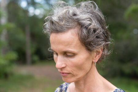 Middle aged woman with grey hair looking down against forest background (selective focus)