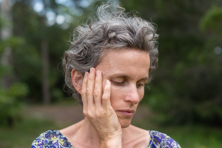 Middle aged woman with grey hair with hand on face against forest background (selective focus) Фото со стока