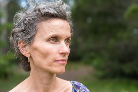 Profile of middle aged woman with grey hair against forest background (selective focus) Фото со стока
