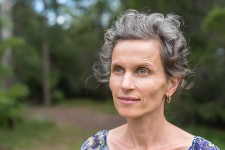 Close up of middle aged woman against forest background (selective focus)