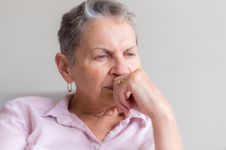 Close up of older woman with short grey hair and pink shirt looking pensive (selective focus)