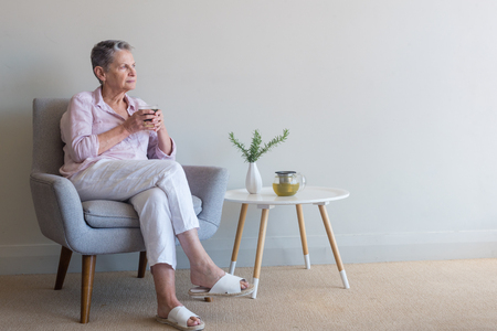 Beautiful older woman sipping tea in retro armchair looking pensive against beige wall