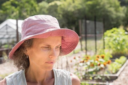 Middle aged woman in sunhat looking pensive in garden (selective focus)