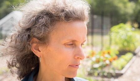 Profile view of natural looking middle aged woman with grey hair in garden (selective focus)