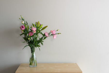 Pink lisianthus flowers and green foliage in glass vase on wooden shelf against beige wall