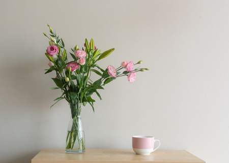 Pink lisianthus flowers in glass vase with mug on wooden shelf against beige wall