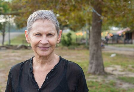 Head and shoulders view of beautiful older woman with short grey hair in park (selective focus)