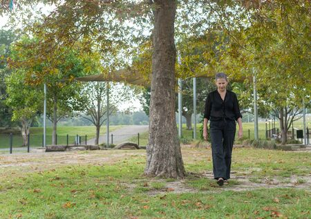Full length view of older woman with short grey hair and black clothing walking in park (selective focus) Фото со стока
