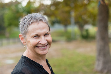 Portrait of beautiful older woman smiling in park (selective focus)